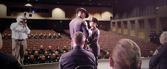 A graduating police recruit receives her badge before a mostly-empty theater.